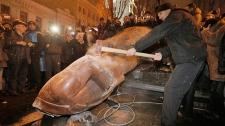 Ukrainian protesters smash a statue of Lenin