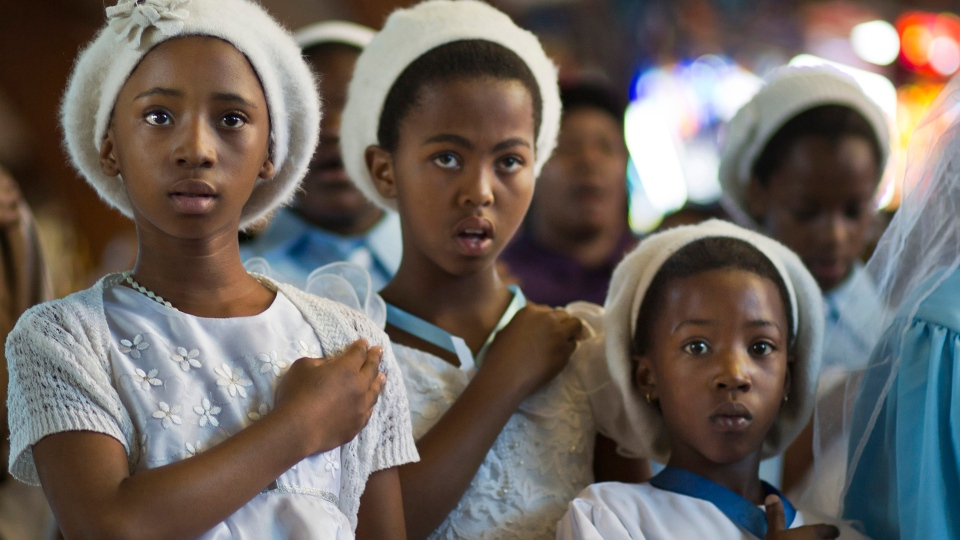 Young members of the choir attend a morning mass in memory of Nelson Mandela at the Regina Mundi church, which became one of the focal points of the anti-apartheid struggle, in Soweto, Johannesburg, South Africa Sunday, Dec. 8, 2013. (AP / Ben Curtis)