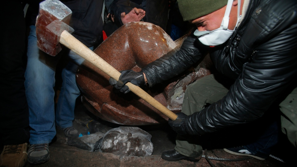 An anti-government protester beats the head of the statue of Vladimir Lenin with a sledgehammer in Kyiv, Ukraine, Sunday, Dec. 8, 2013. (AP / Sergei Grits)