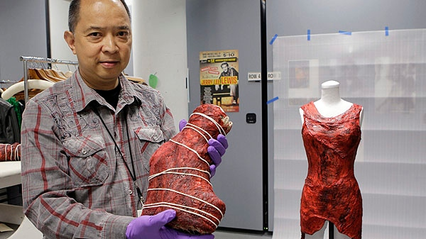 In this photo taken June 14, 2011, Jun Francisco, director of collections management at the Rock and Roll Hall of Fame and Museum, displays a boot and dress made of meat worn by Lady Gaga in the museum's vault. (AP Photo/Mark Duncan)