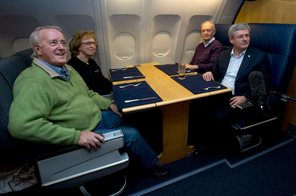 Prime Minister Stephen Harper speaks with former prime ministers Brian Mulroney, Kim Campbell and Jean Chretien on board a government plane travelling to South Africa Sunday, Dec. 8, 2013. (Adrian Wyld  / THE CANADIAN PRESS)