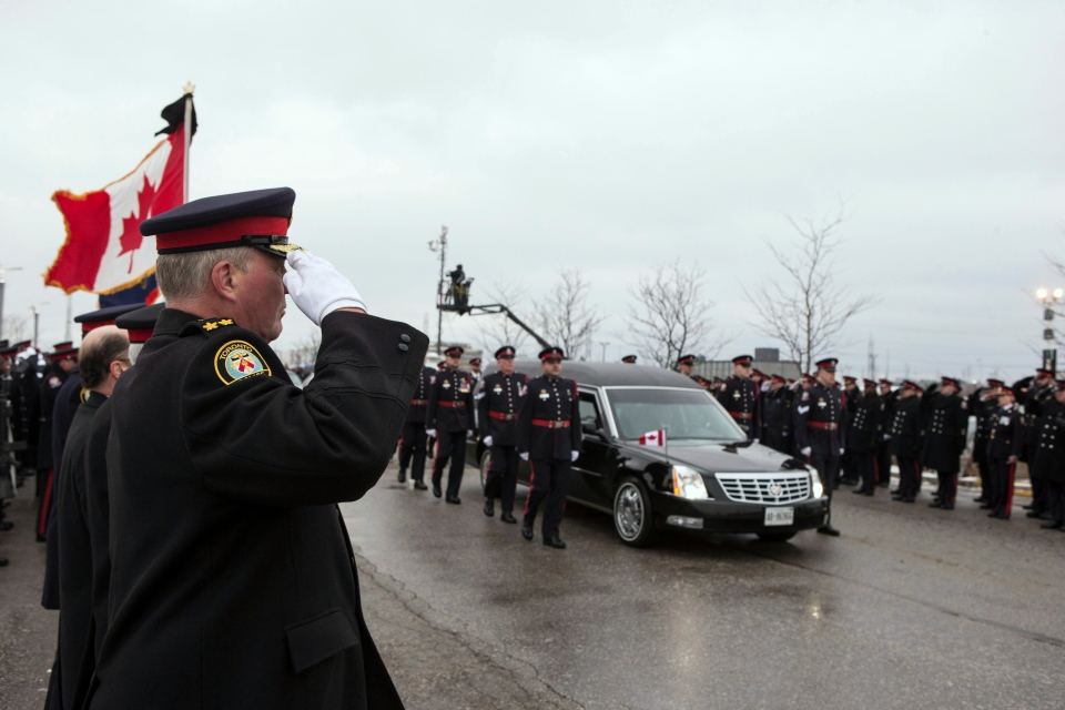 Toronto Police Chief Bill Blair, left, and fellow officers line the route as the hearse containing Const. John Zivcic's casket arrives at his memorial service in Toronto on Monday, Dec. 9, 2013. (Chris Young / THE CANADIAN PRESS)
