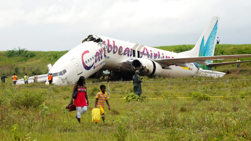 The broken fuselage of a Caribbean Airlines' Boeing 737-800 is seen after it crashed at the end of the runway at Cheddi Jagan International Airport in Timehri, Guyana, Saturday, July 30, 2011. (AP / Jules Gibson)