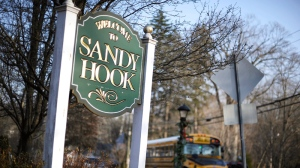 A school bus drives past a lamppost decorated for the holidays, and a sign reading Welcome to Sandy Hook, in Newtown, Conn., Wednesday, Dec. 4, 2013.  (AP / Jessica Hill)
