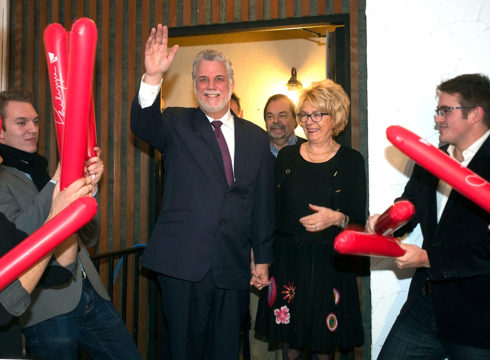 Quebec Liberal party leader Philippe Couilliard waves to supporters as his wife, Suzanne, looks on after winning the byelection in Outremont riding Monday, December 9, 2013 in Montreal.THE CANADIAN PRESS/Ryan Remiorz