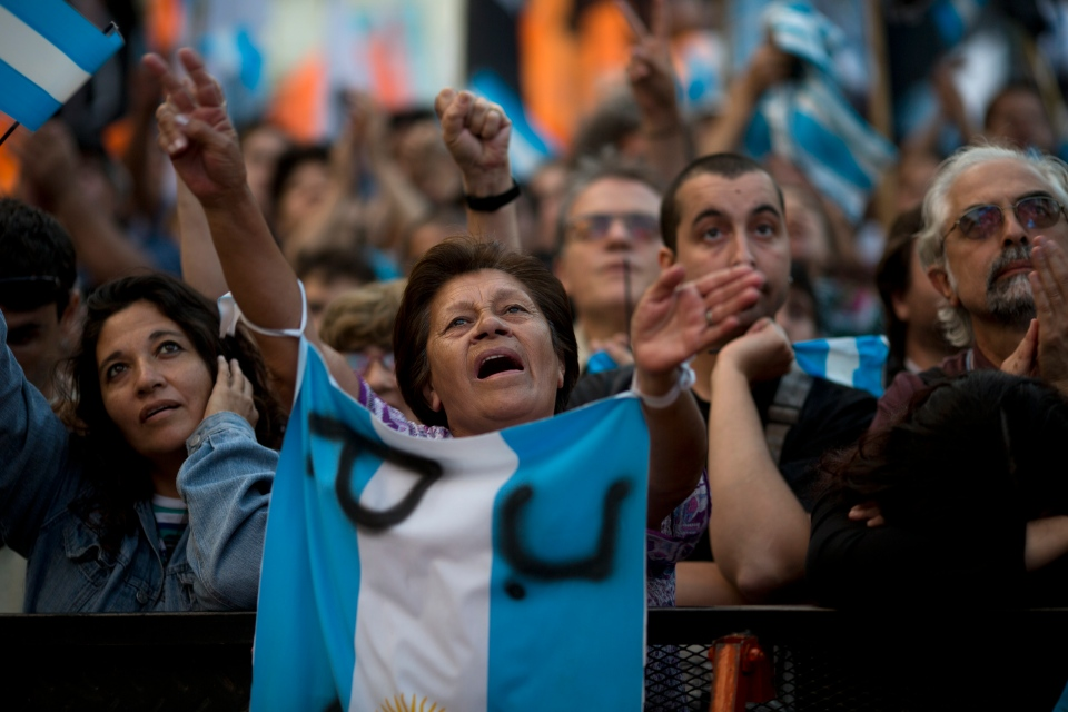 A woman holds an Argentine flag during the 30 year anniversary of the return of the democracy celebration at Plaza de Mayo square in Buenos Aires, Argentina, Tuesday, Dec. 10, 2013. (AP /Rodrigo Abd)
