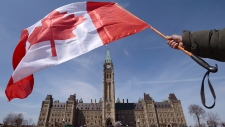 A Canadian flag attached to a ski pole is waved on Parliament Hill in Ottawa on Monday, April 15, 2013. (The Canadian Press/Sean Kilpatrick)