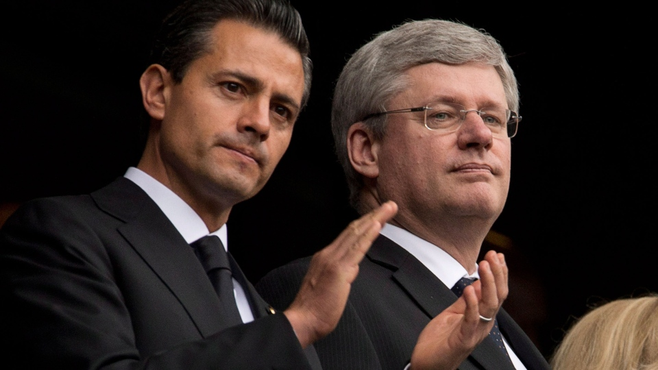 Canadian Prime Minister Stephen Harper stands next to Mexican President Enrique Pena Nieto during a memorial service for Nelson Mandela in Johannesburg, South Africa on Tuesday, Dec. 10, 2013. (Adrian Wyld / THE CANADIAN PRESS)