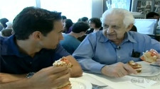 CTV Montreal's Rob Lurie (left) enjoys a lox and cream cheese sandwich with Hymie Sckolnick, who turned 90 on Monday and has been selling the sandwiches at Beauty's for nearly 70 years.