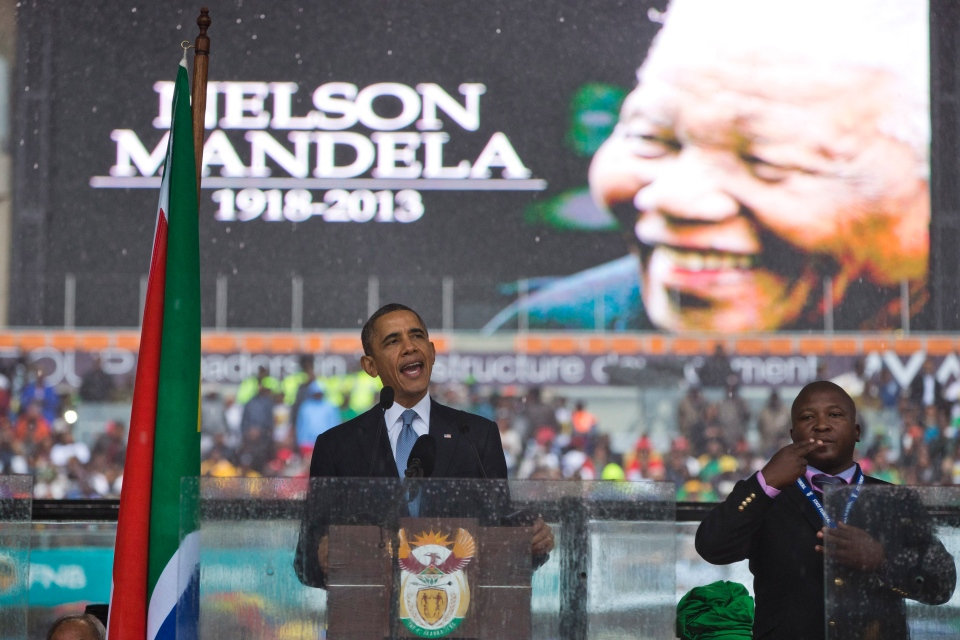 U.S. President Barack Obama delivers his speech next to a sign language interpreter during a memorial service at FNB Stadium in honor of Nelson Mandela in Soweto, near Johannesburg on Tuesday, Dec. 10, 2013. (AP /  Evan Vucci)