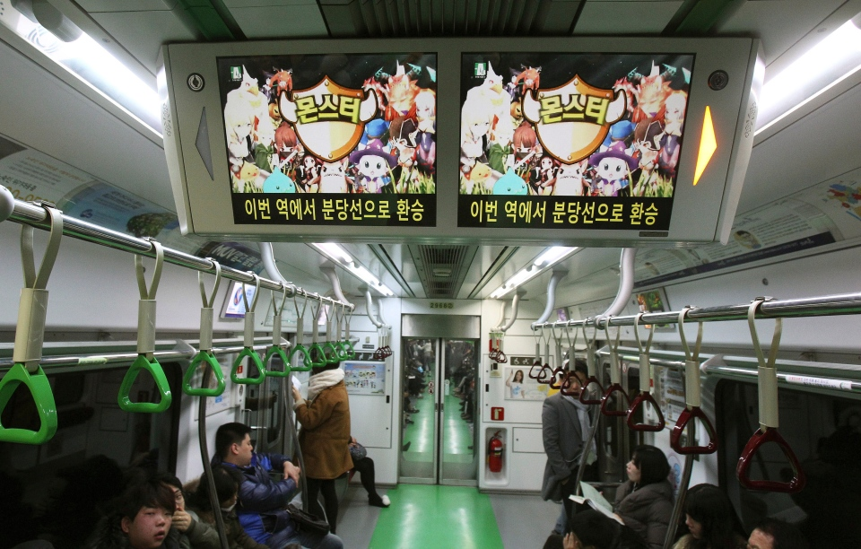 Screens advertising an online mobile game are displayed in a subway train in Seoul, South Korea, Wednesday, Dec. 11, 2013.(AP Photo/Ahn Young-joon)