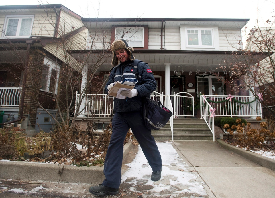 A Canada Post employee delivers mail and parcels to residential homes in Toronto on Wednesday, Dec. 11, 2013. (THE CANADIAN PRESS / Nathan Denette)