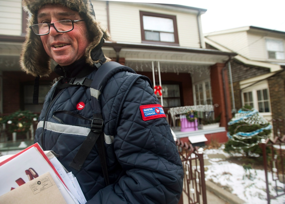 A Canada Post employee delivers mail in Toronto on Dec. 11, 2013. (THE CANADIAN PRESS / Nathan Denette)