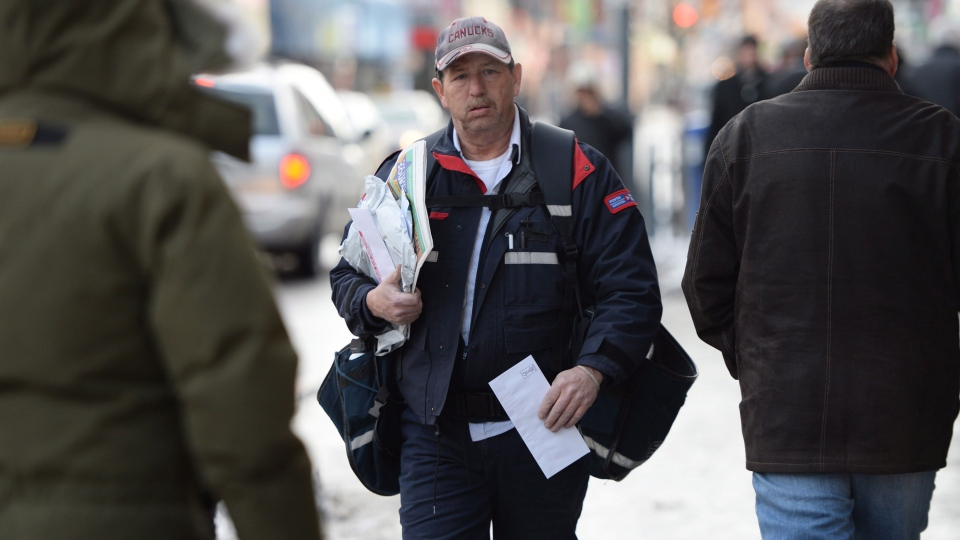 A Canada Post mail carrier walks in Ottawa, Wednesday, Dec.11, 2013. (Sean Kilpatrick / THE CANADIAN PRESS)