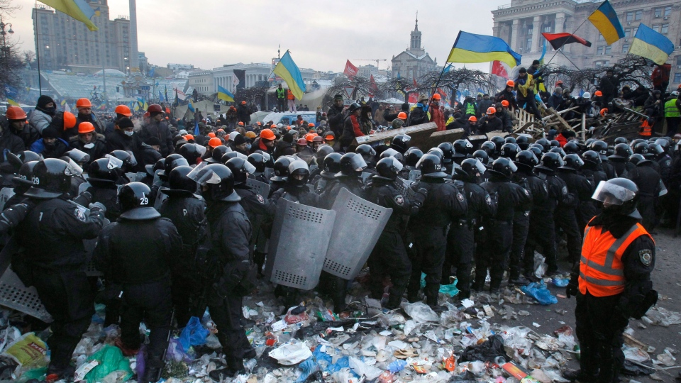 Pro-European Union activists wave flags as riot police pull back from Independence Square in Kyiv, Ukraine, Wednesday, Dec. 11, 2013. (AP / Sergei Grits)