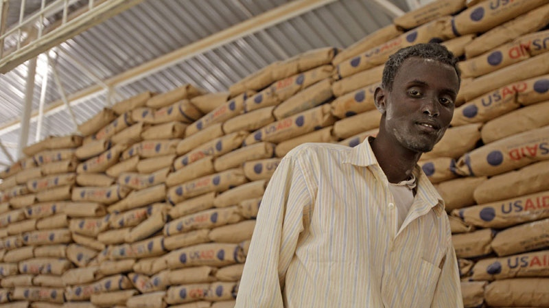 A worker stands next to bags of food to hand out to refugees inside a food distribution center run by the World Food Programme (WFP), in the town of Dadaab, Kenya, Tuesday, Aug. 2, 2011. (AP Photo/Schalk van Zuydam)