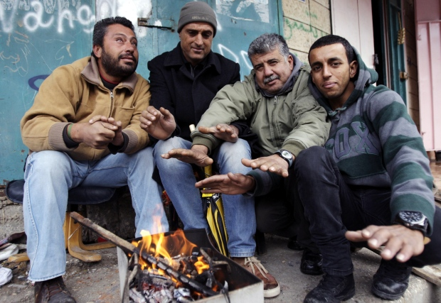 Palestinian men gather around to warms their hands