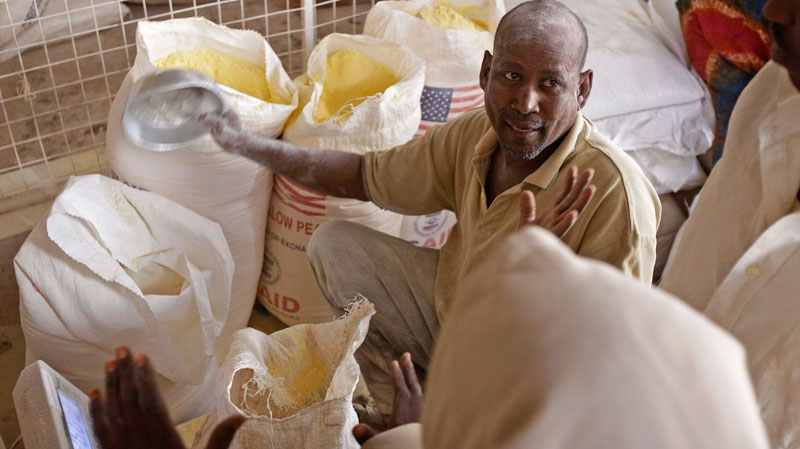 A worker hands out food to refugees inside a food distribution center run by the World Food Programme (WFP), in the town of Dadaab, Kenya, Tuesday, Aug. 2, 2011. (AP / Schalk van Zuydam)