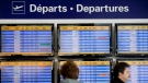 Passengers stand next to a departures board at Trudeau Airport in Montreal, Friday, April 13, 2012. THE CANADIAN PRESS/Graham Hughes