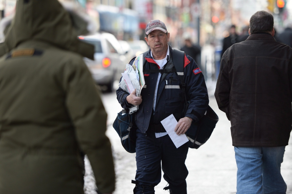 A mail carrier walks in Ottawa, Wednesday, Dec.11, 2013. (Sean Kilpatrick / THE CANADIAN PRESS)