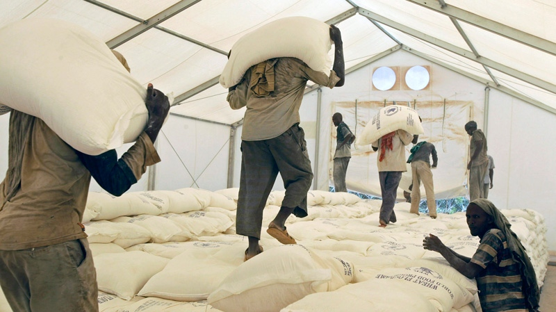 Workers carry sacks of food at a food distribution center run by the World Food Programme (WFP), in the town of Dadaab, Kenya, Tuesday, Aug 2, 2011. (AP / Schalk van Zuydam)