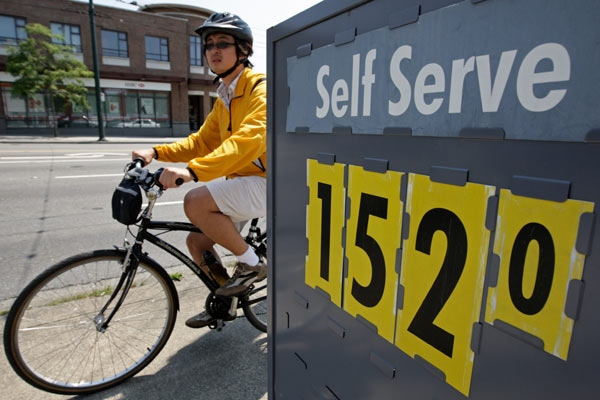 A cyclist passes a sign advertising the price of gasoline at $1.52 per litre at a gas station in Vancouver, B.C., on Tuesday July 1, 2008. (Darryl Dyck / THE CANADIAN PRESS)