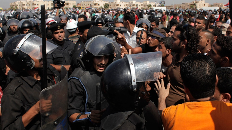 Anti-Mubarak protesters scuffle with riot police outside the Police Military Academy complex in Cairo, Egypt Wednesday, Aug. 3, 2011. (AP / Nasser Nasser)