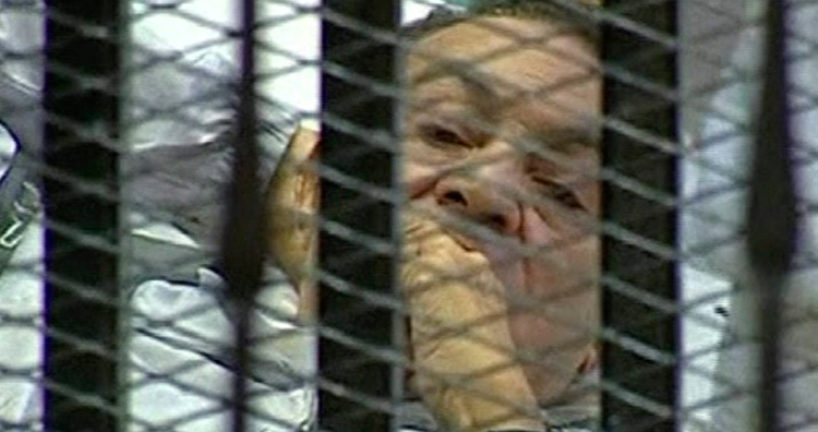 83-year-old former Egyptian president Hosni Mubarak laying on a hospital bed inside a cage of mesh and iron bars in a Cairo courtroom, Wednesday, Aug. 3, 2011. (Egyptian State TV)