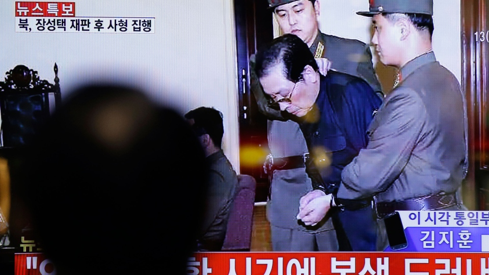 A man watches a live TV news program showing that North Korean leader Kim Jong Un's uncle Jang Song Thaek, second from right, is escorted by military officers during a trial in Pyongyang, North Korea Thursday, Dec. 12, 2013, at the Seoul Railway Station in Seoul, South Korea, Friday, Dec. 13, 2013. (AP / Lee Jin-man)