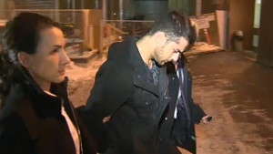 Calgary Police escort Assmar Ryiad Shlah, 20, into the Arrest Processing Unit on December 12, 2013.