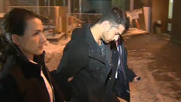 Calgary Police escort Assmar Ryiad Shlah, 20, into the Arrest Processing Unit on December 12, 2013.