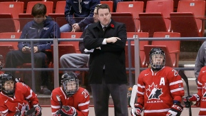 Team Canada coach Dan Church stands on the bench during the third period of a Four Nations Cup women's hockey game on Wednesday, Nov. 6, 2013, in Lake Placid, N.Y. Canada won 4-2. (AP / Mike Groll)