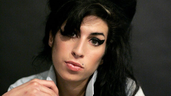 In this Friday Feb. 16, 2007 file photo British singer Amy Winehouse poses for photographs after being interviewed by the Associated Press at a studio in north London.  (AP / Matt Dunham, File)