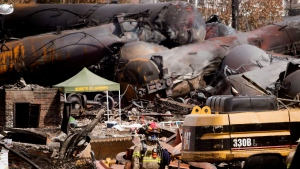 A fireman walks through the debris as work continues at the crash site of the train derailment and fire Tuesday, July 16, 2013 in Lac-Megantic, Que. that left 37 people confirmed dead and another 13 missing and presumed dead. (Ryan Remiorz / THE CANADIAN PRESS)