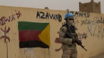 In this Sunday, July, 28, 2013 file photo, a United Nations peacekeeper stands guard at the entrance to a polling station covered in separatist flags and graffiti in Kidal, Mali. (AP Photo/Rebecca Blackwell, File)