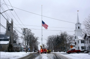 On the first anniversary of the Sandy Hook massacre, firefighters lower the town's flag on Main Street to half-staff in honor of the victims, in Newtown, Conn., Saturday, Dec. 14, 2013. (AP / Robert F. Bukaty)