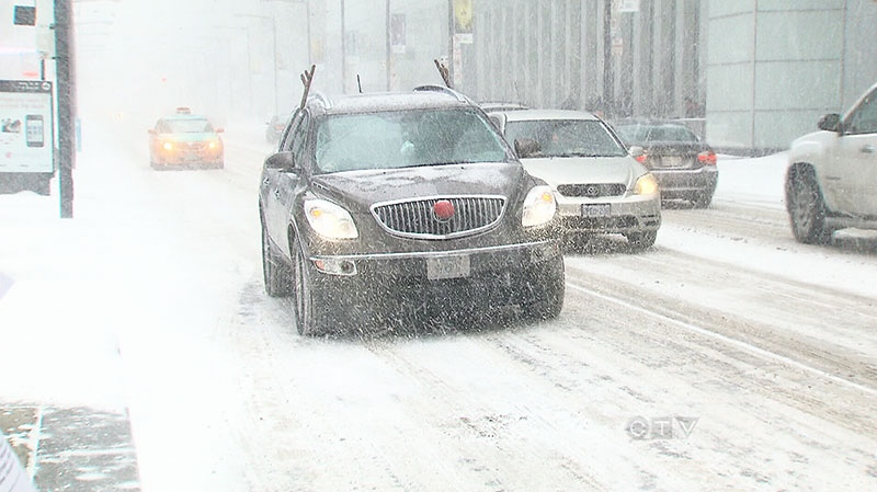 Drivers move slowly on the roads as snow pounds the ground in Toronto on Saturday, Dec. 14, 2013.