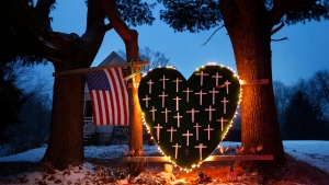 A makeshift memorial with crosses for the victims of the Sandy Hook massacre stands outside a home in Newtown, Conn., Saturday, Dec. 14, 2013, the one-year anniversary of the shootings. (AP / Robert F. Bukaty)