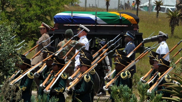 A military honor guard escorts former South African president Nelson Madela funeral cortege on its way to its burial site in his home village of Qunu, South Africa, Sunday, Dec. 15, 2013. (Elmond Jiyane, CGIS)