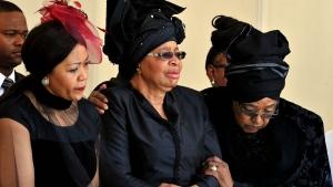 From left: Tobeka Zuma, Nelson Mandela's widow Graca Machel, and Winnie Madikizela-Mandela, Nelson Mandela's former wife, watch as former South African President Nelson Mandela's casket arrives at his burial site following his funeral service in Qunu, South Africa, Sunday, Dec. 15, 2013. (Elmond Jiyane, GCIS)