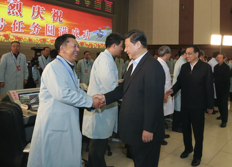 In this photo released by China's Xinhua News Agency, Chinese President Xi Jinping and Chinese Premier Li Keqiang shake hands with scientists to congratulate them on the success of the Chang'e 3 mission at the Beijing Aerospace Control Center in Beijing, China, Sunday, Dec. 15, 2013. (AP Photo/Xinhua, Ding Lin)