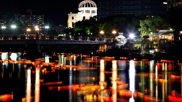 Against the backdrop of the Atomic Bomb Dome, paper lanterns float down along Motoyasu River at Hiroshima Peace Memorial Park in Hiroshima, western Japan, Saturday, Aug. 6, 2011. (AP / Koji Sasahara)
