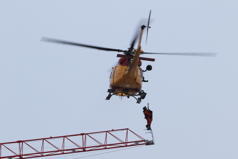 A search and rescue helicopter rescues a crane operator during a fire in downtown Kingston, Ont., on Dec.17, 2013. (Lars Hagberg / THE CANADIAN PRESS)