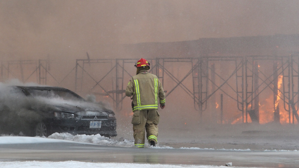 A firefighter surveys the scene during a major fire in downtown Kingston, Ont., Tuesday, Dec.17, 2013. (Lars Hagberg / THE CANADIAN PRESS)