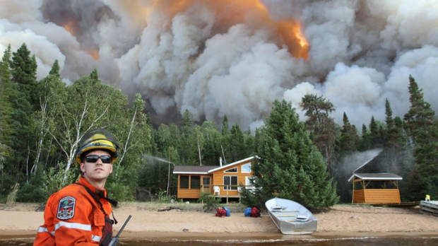 Ministry of Natural Resources fire ranger Warren Okanski looks back as a camp protected by sprinklers is threatened by a forest fire near the town of Red Lake, Ont., on Thursday, August 4, 2011. (HO - Ontario Ministry of Natural Resources - Mitch Miller / THE CANADIAN PRESS)