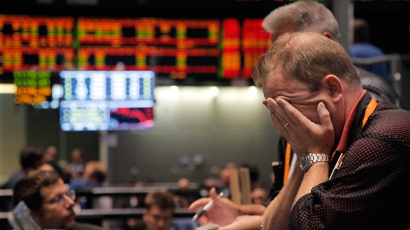 Trader Andrew Stavros reacts after the close of trading in the NASDAQ, 100 Index pit, on the floor of The CME Group in Chicago on Monday, Aug. 8, 2011. (AP / M. Spencer Green)