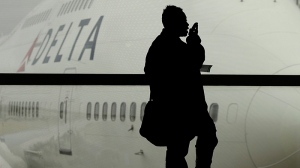 In this Oct. 29, 2012, file photo, a traveller on Delta Air Lines waits for her flight in Detroit. (AP Photo/Charlie Riedel, File)
