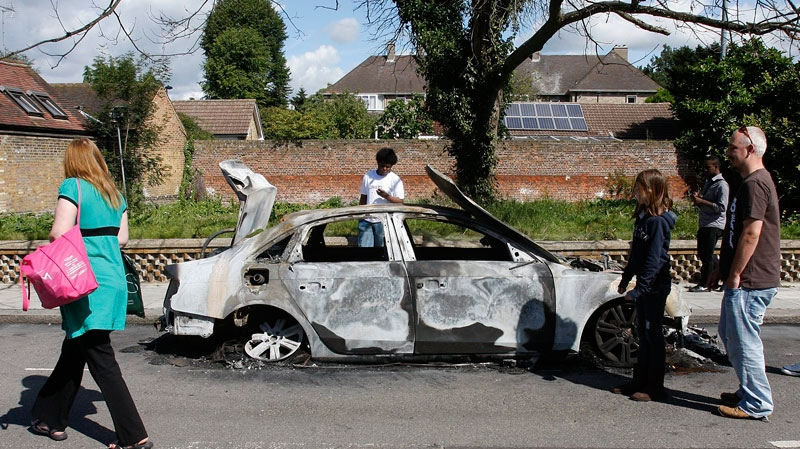Local inhabitants view the shell of a burnt-out car in Enfield, north London, Monday, Aug. 8, 2011. (AP / Akira Suemori)