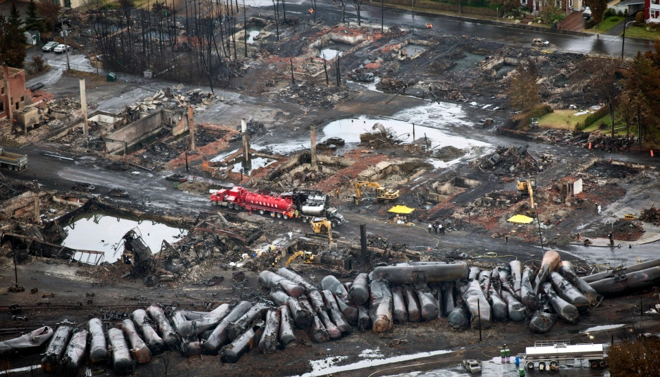 In this July 9, 2013 file photo, workers comb through debris after an unmanned train with 72 railway cars carrying crude oil derailed Saturday causing explosions in Lac-Megantic, Quebec. (AP /The Canadian Press, Paul Chiasson)