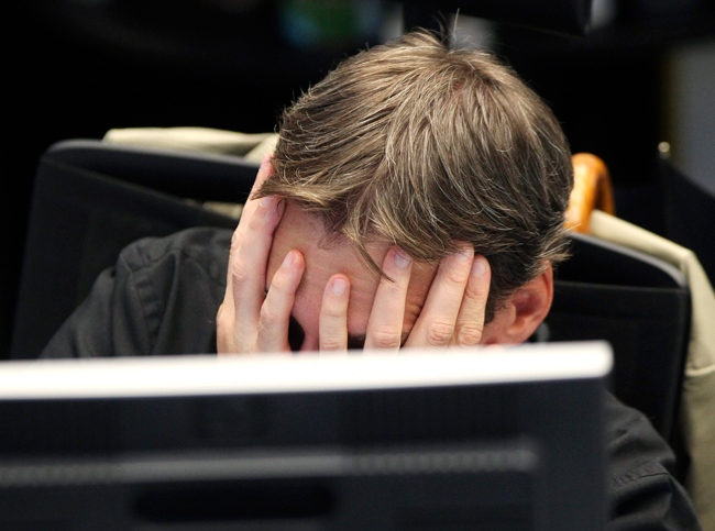 A broker covers his face behind his screen at the stock market in Frankfurt, Germany, Monday, Aug.8, 2011. (AP / Michael Probst)